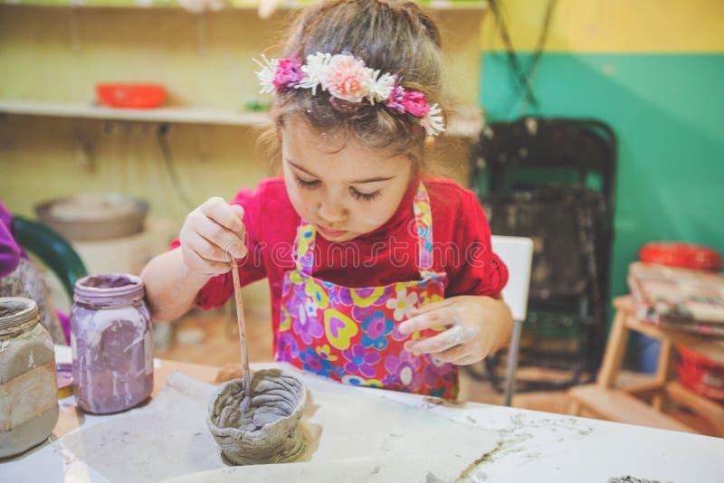 Niña en el taller de la cerámica que pinta a Clay Vase imágenes de archivo libres de regalías