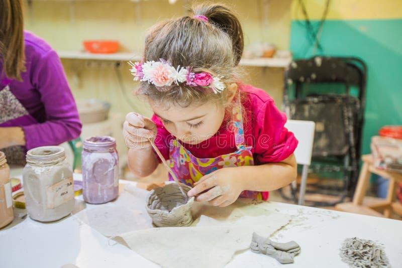 Niña en el taller de la cerámica que pinta a Clay Vase imagen de archivo
