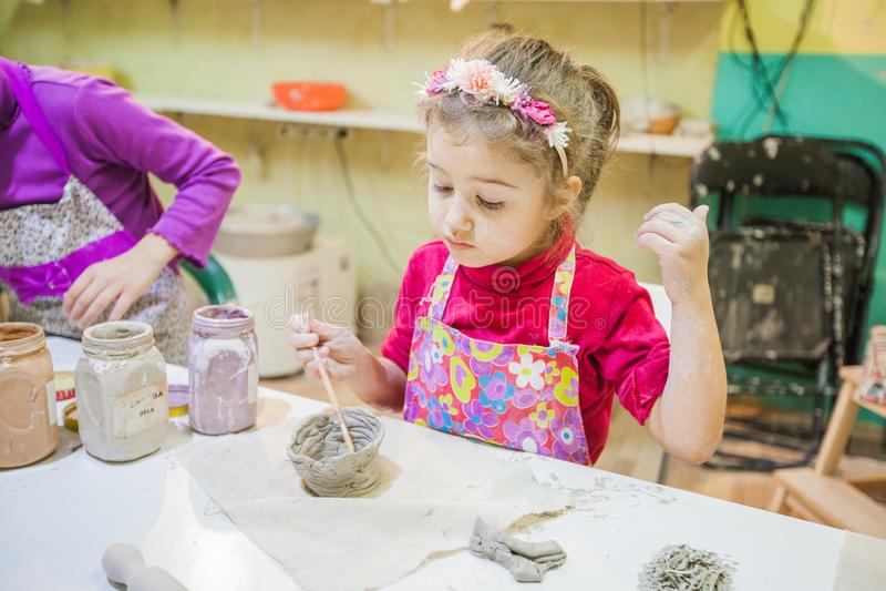 Niña en el taller de la cerámica que pinta a Clay Vase fotos de archivo libres de regalías
