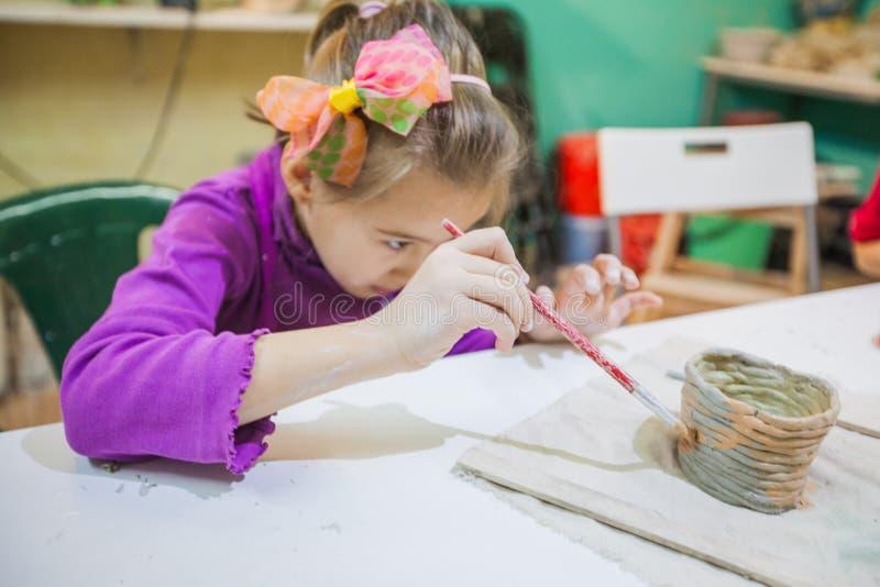 Niña en el taller de la cerámica que pinta a Clay Vase fotografía de archivo libre de regalías