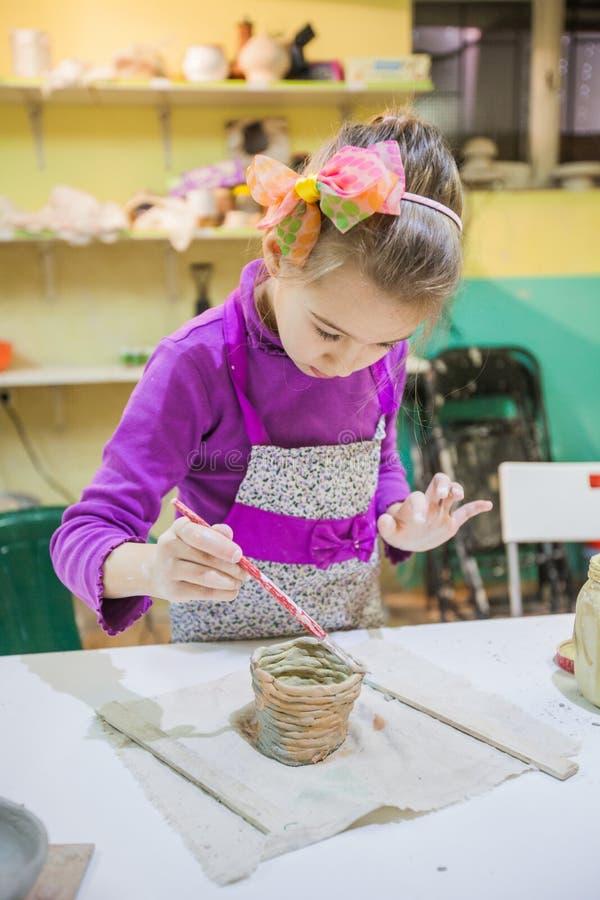 Niña en el taller de la cerámica que pinta a Clay Vase fotografía de archivo