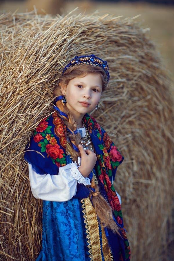 Niña en el traje ruso en el campo fotos de archivo