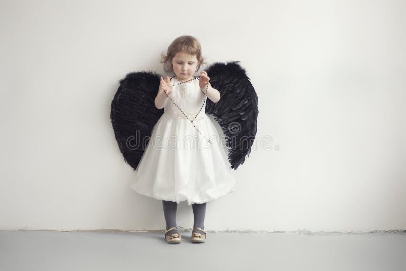 Niña en el vestido blanco con las alas negras artificiales fotografía de archivo libre de regalías