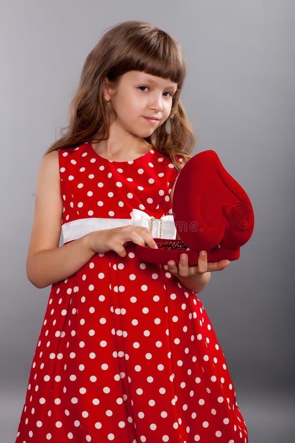 Niña en el vestido rojo que lleva a cabo su presente imagen de archivo