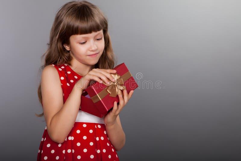 Niña en el vestido rojo que lleva a cabo su presente imágenes de archivo libres de regalías