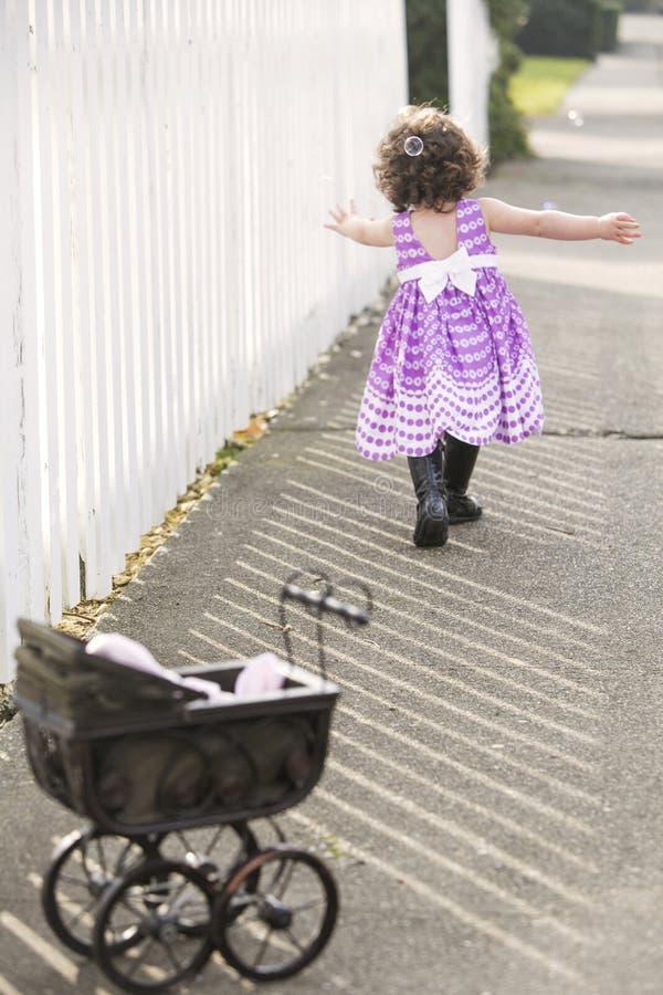 Niña en el vestido rosado que persigue burbujas de jabón foto de archivo libre de regalías