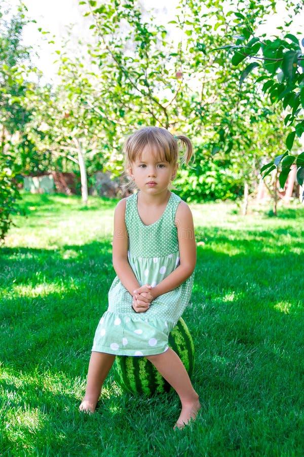 Niña en el vestido verde que se sienta en la sandía en el parque, al aire libre Verano Niño triste fotografía de archivo libre de regalías