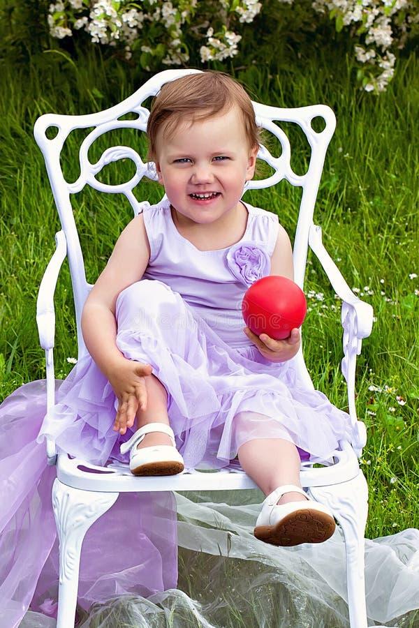 Niña en el vestido violeta con la bola roja imágenes de archivo libres de regalías