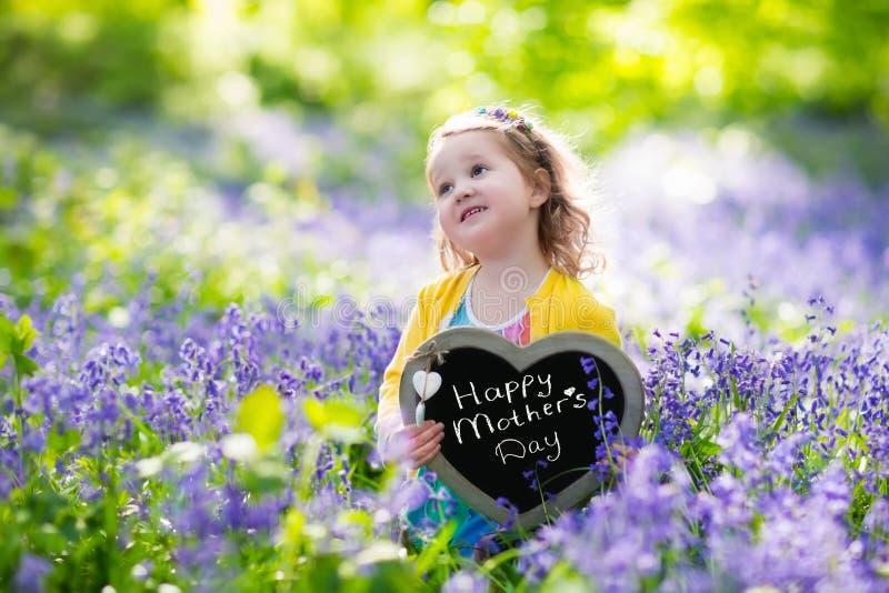 Niña en flores de los bluebelss imagen de archivo