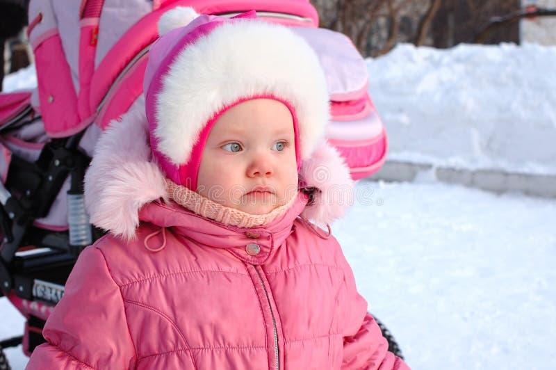 Niña en fondo de la nieve y el carro de bebé. imágenes de archivo libres de regalías
