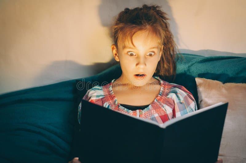 niña en la cama por la noche lee un terrible libro místico asombroso en la oscuridad imagenes de archivo