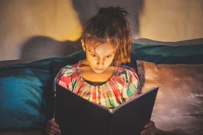 niña en la cama por la noche lee un terrible libro místico asombroso en la oscuridad imágenes de archivo libres de regalías