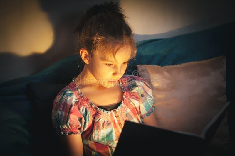 niña en la cama por la noche lee un terrible libro místico asombroso en la oscuridad fotografía de archivo libre de regalías