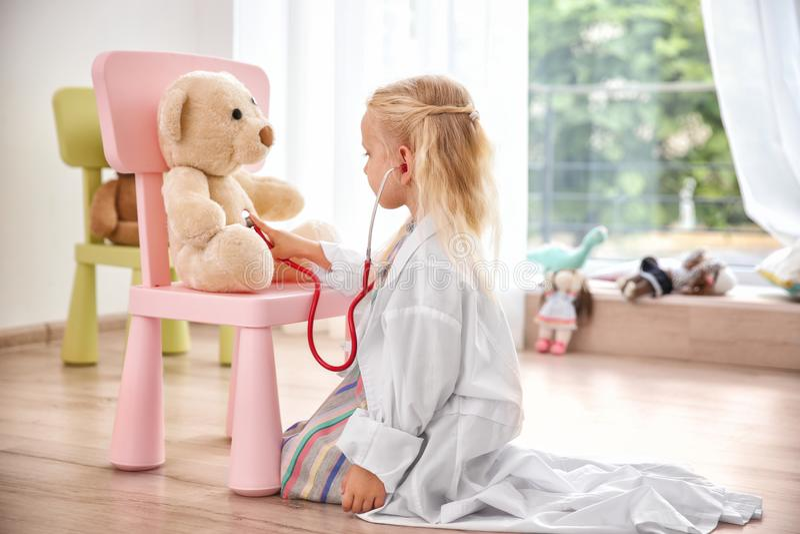 Niña en la capa médica que juega con el oso de peluche fotos de archivo