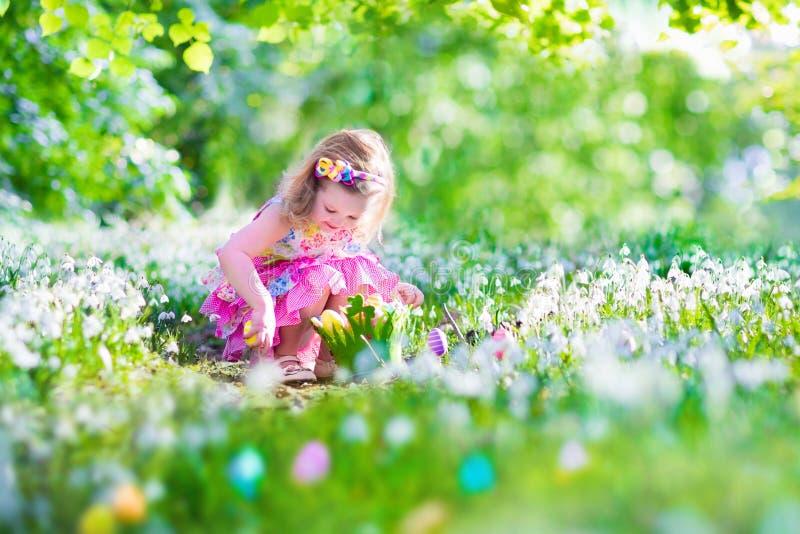 Niña en la caza del huevo de Pascua fotografía de archivo