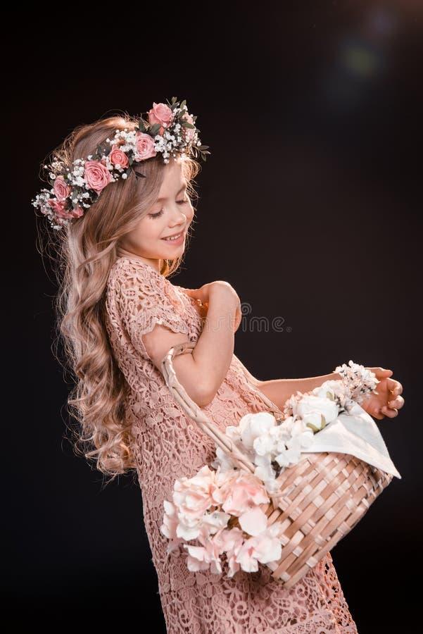 Niña en la guirnalda floral que sostiene la cesta de la flor en negro fotos de archivo libres de regalías
