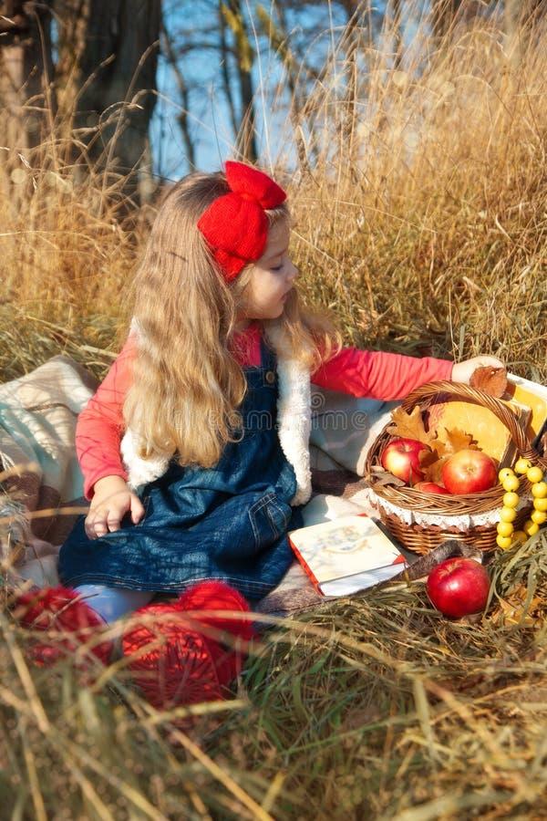 Niña en la naturaleza con una cesta de fruta y imagenes de archivo