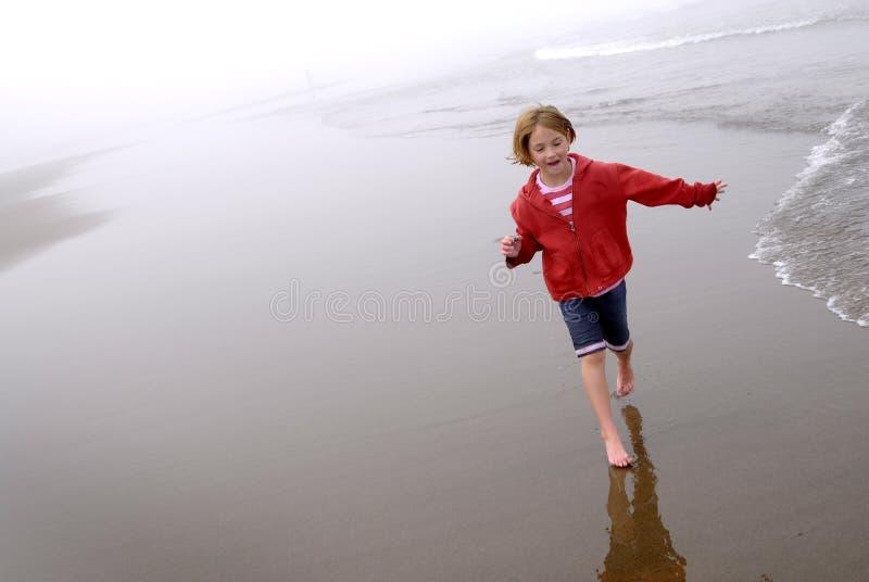 Niña en la playa de niebla que lleva la chaqueta roja imagen de archivo