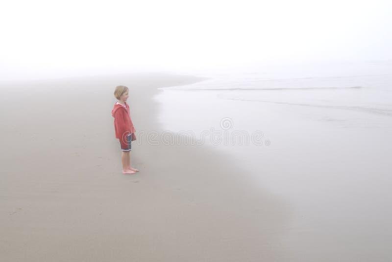 Niña en la playa de niebla que lleva la chaqueta roja imágenes de archivo libres de regalías