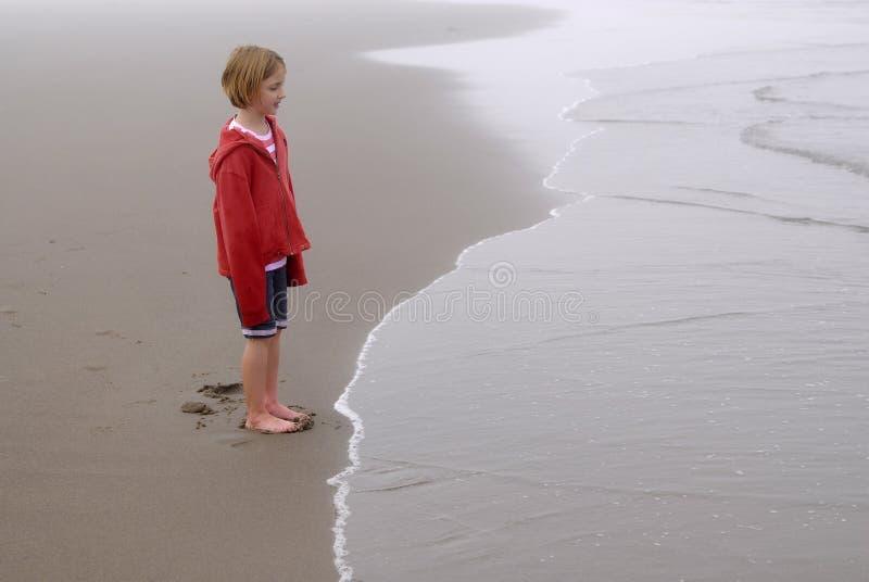 Niña en la playa de niebla que lleva la chaqueta roja foto de archivo