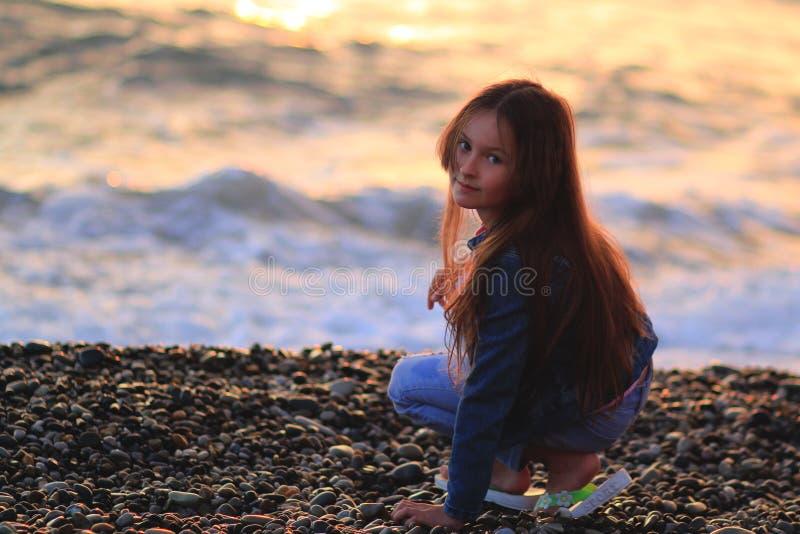 Niña en la playa, puesta del sol, pelo largo imagen de archivo