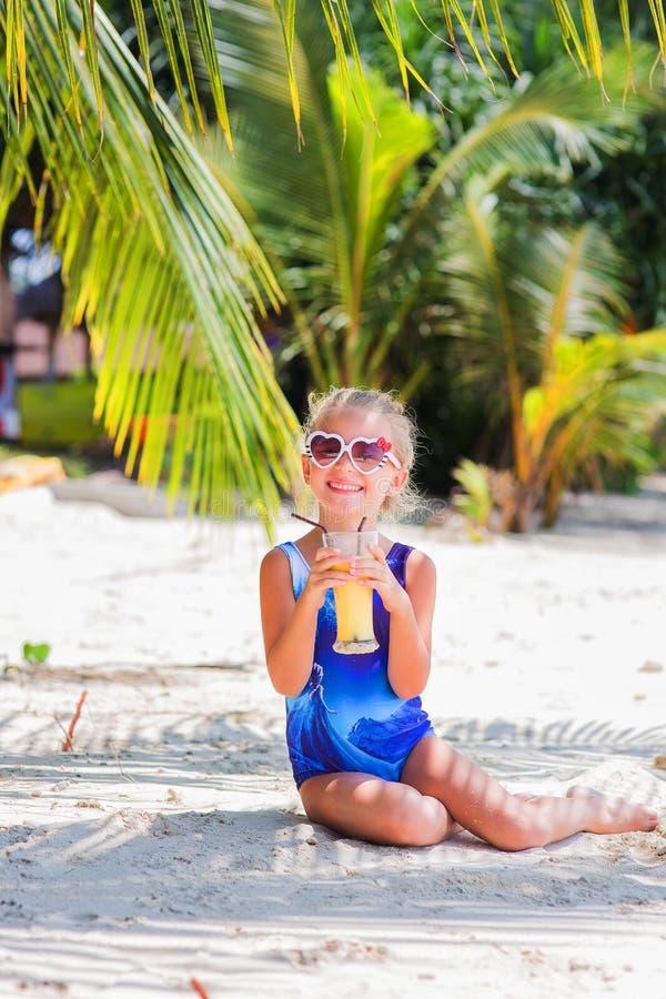 Niña en la playa que bebe el cóctel exótico, mar, océano, bikini, verano, tropical, al aire libre, en cámara de mirada imagen de archivo libre de regalías