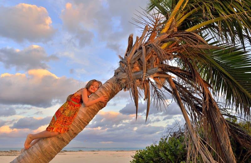 Niña en la playa tropical que se sienta en la palmera imagen de archivo