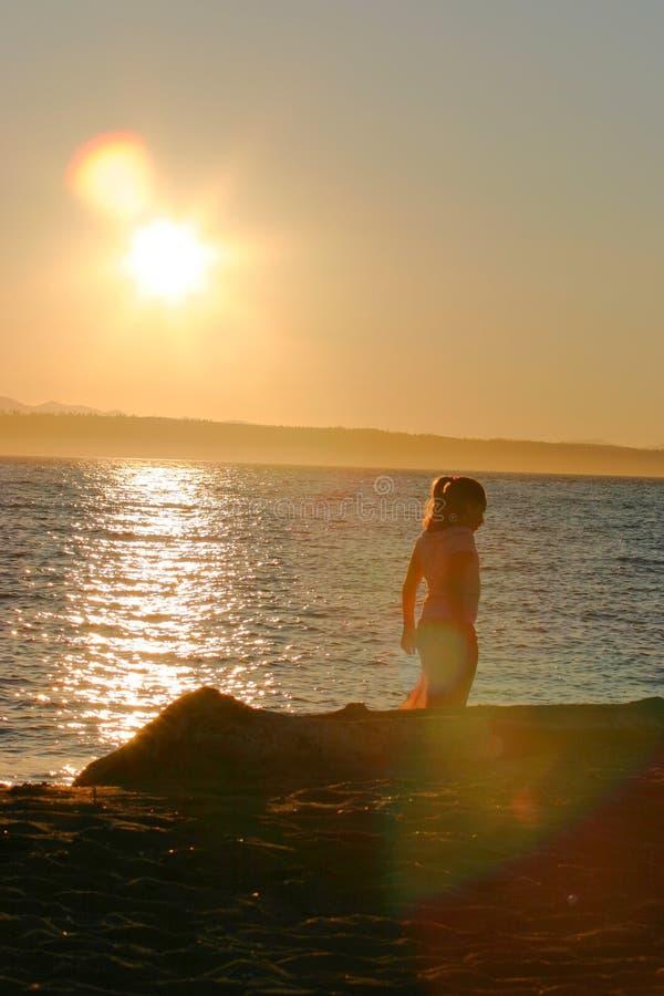 Niña en la puesta del sol foto de archivo