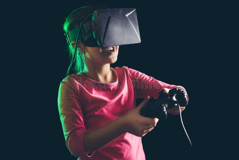 Niña en las auriculares de la realidad virtual que juegan el videojuego fotos de archivo