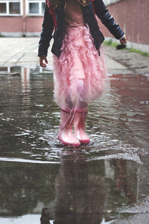 Niña en las botas de goma, jugando en pequeño charco después de lluvia foto de archivo