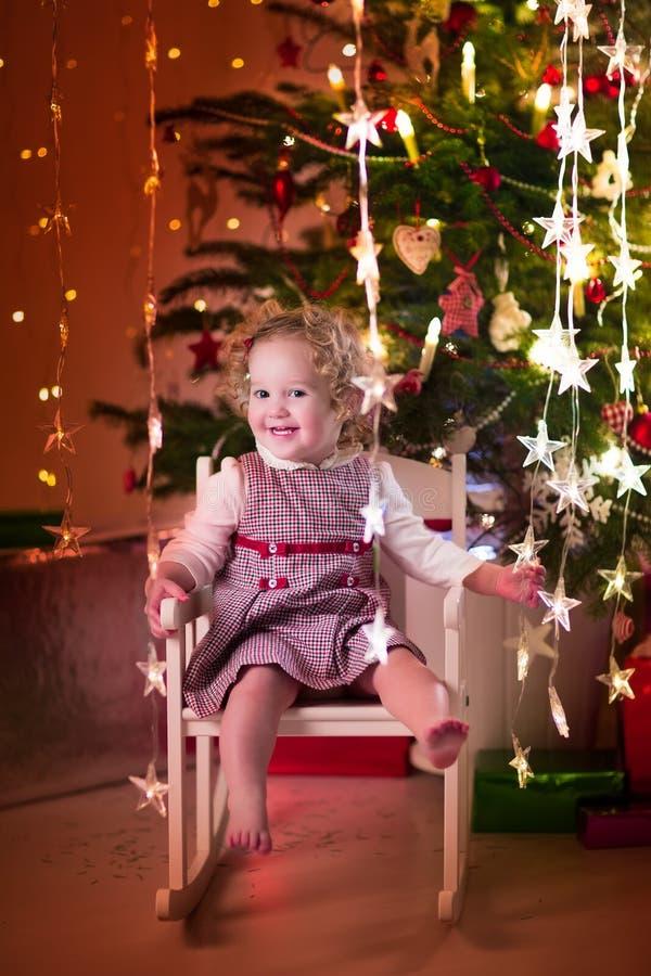Niña en mecedora debajo del árbol de navidad foto de archivo