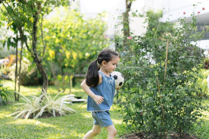 Niña en parque de naturaleza tenencia linda del niño que juega a fútbol imagen de archivo