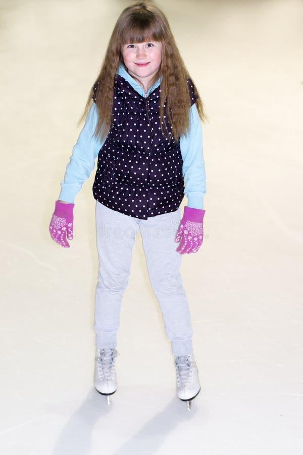 Niña en patines en el hielo foto de archivo