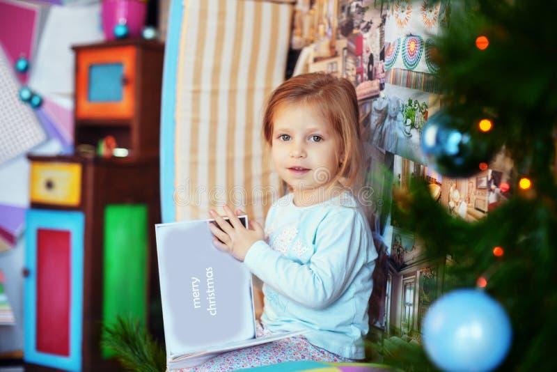 Niña en pijamas que lee un libro por la mañana El concep fotografía de archivo libre de regalías