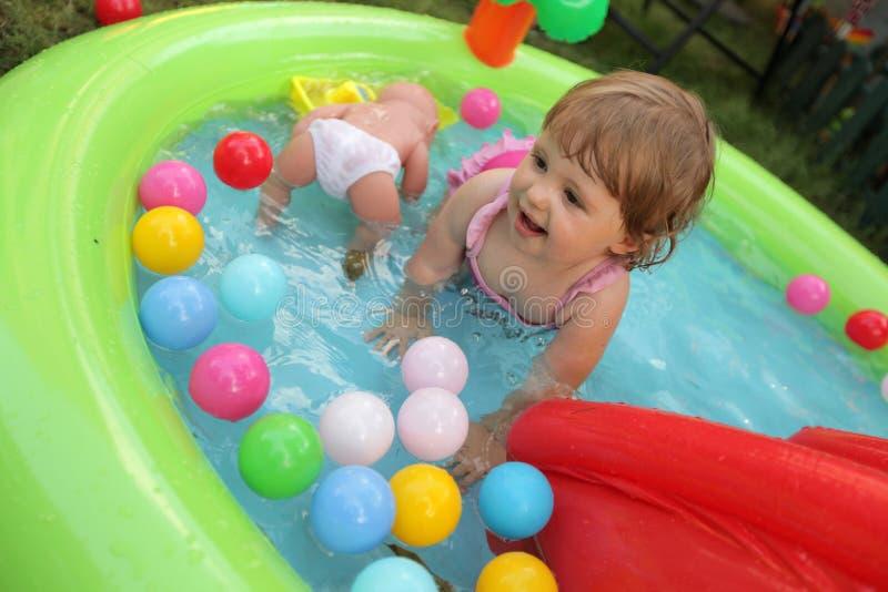 Niña en piscina de los niños imagenes de archivo