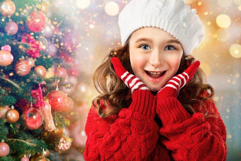 Niña en ropa del invierno sorprendida cerca del árbol de navidad fotografía de archivo