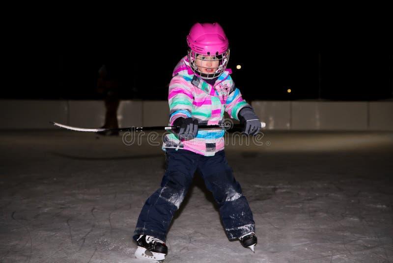 Niña en rosa en engranaje del hockey fotografía de archivo