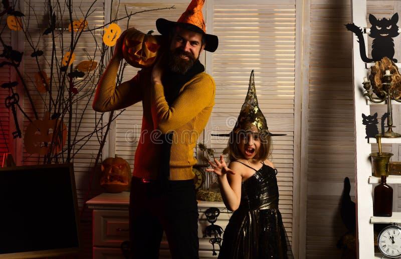 Niña en sombrero del wiz con las manos espeluznantes La niña y el padre hacen magia del wiz La familia feliz celebra Halloween Fe imagenes de archivo
