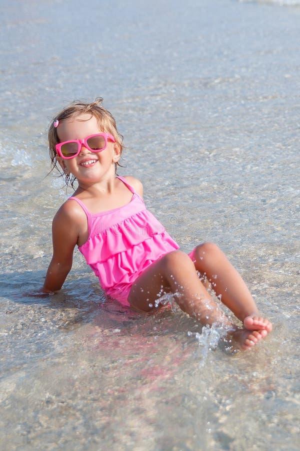 Niña en traje de baño rosado y las gafas de sol que se sientan en el mar que presenta en la cámara Feliz, sonriendo Vacaciones de imagenes de archivo