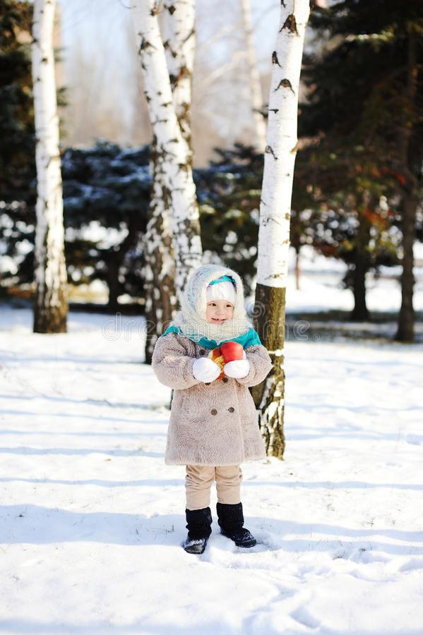 Niña en un abrigo de pieles y mantones mullidos de Orenburg con un app imagen de archivo libre de regalías