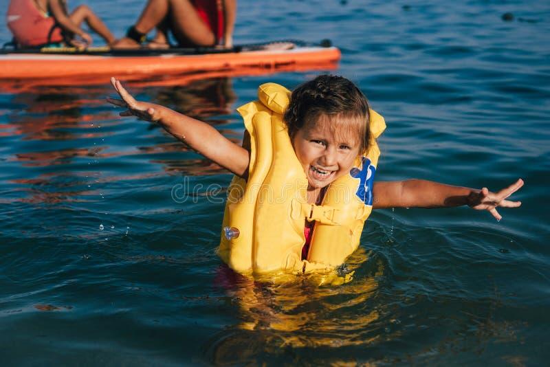 Niña en un chaleco salvavidas bañarse en el mar imagen de archivo libre de regalías