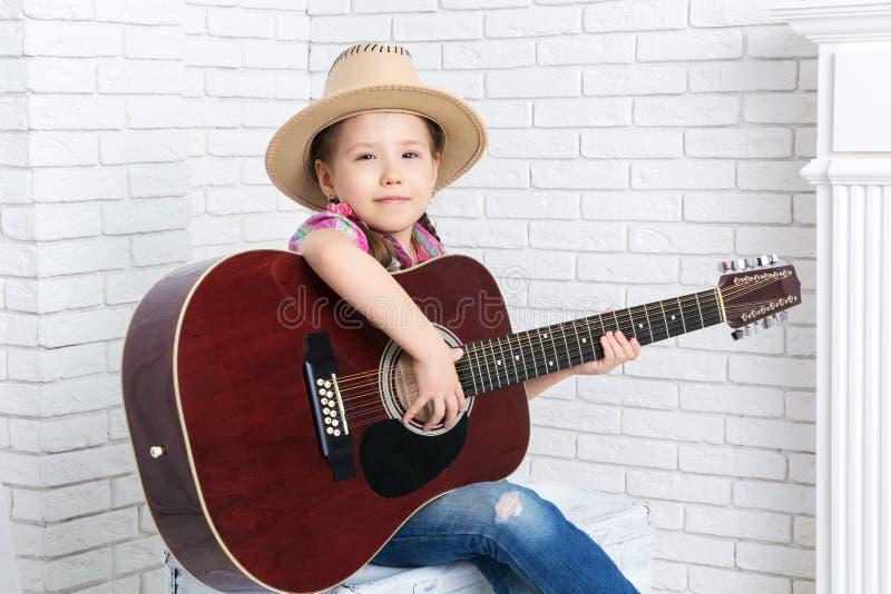 Niña en un sombrero de vaquero con su guitarra imagen de archivo