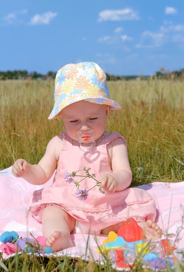 Niña en un sombrero que se sienta en campo verde fotos de archivo libres de regalías