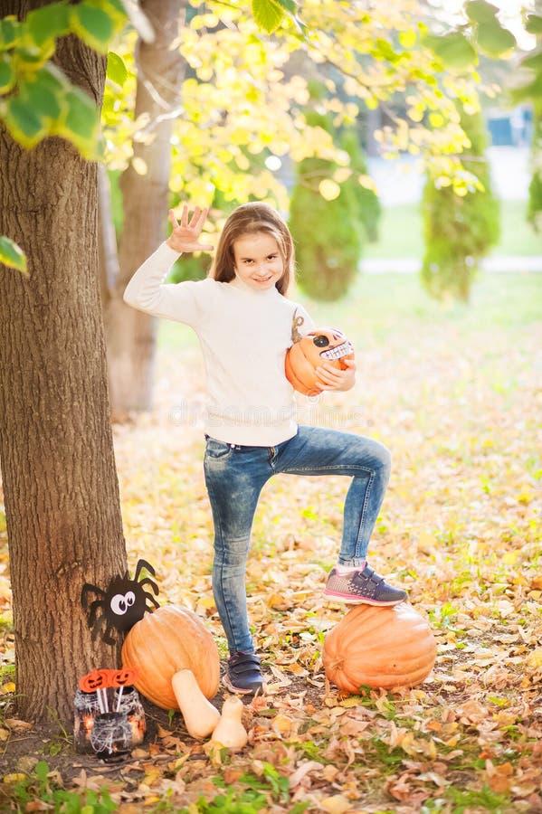 Niña en un suéter blanco y vaqueros en un fondo del fondo natural de textura verde Una muchacha sobre las calabazas y conjura fotos de archivo libres de regalías