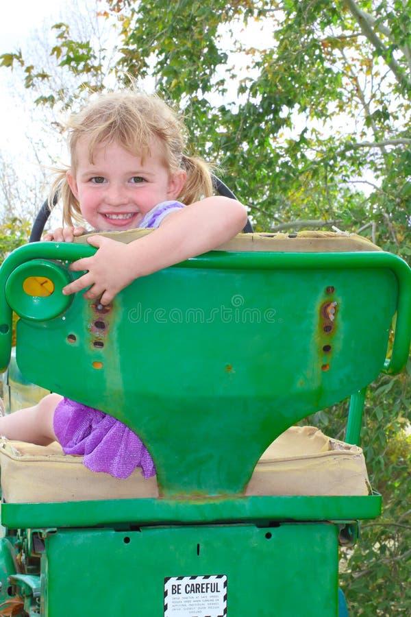 Niña en un tractor verde imagenes de archivo