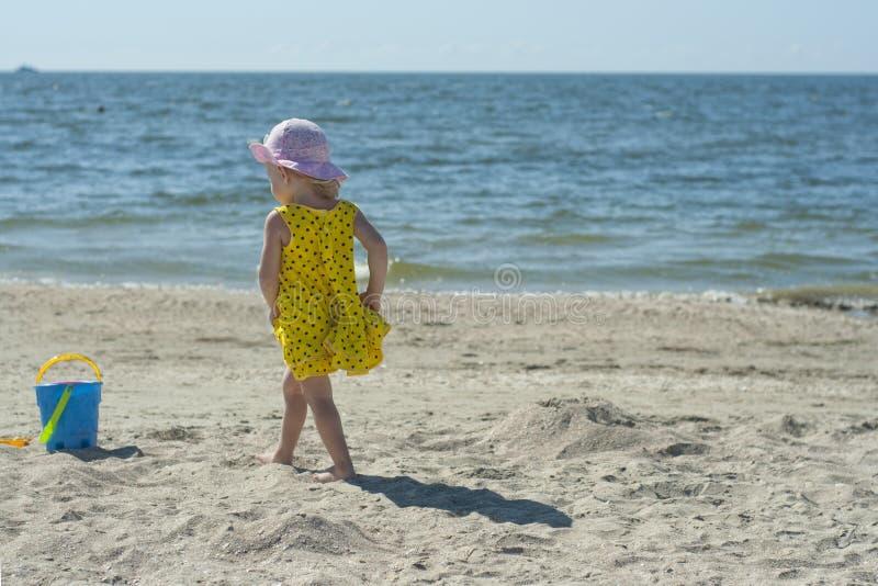 Niña en un vestido amarillo en la playa fotografía de archivo libre de regalías