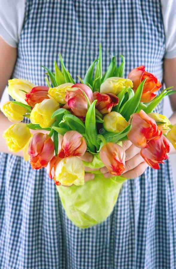 Niña que da un ramo de tulipanes fotos de archivo