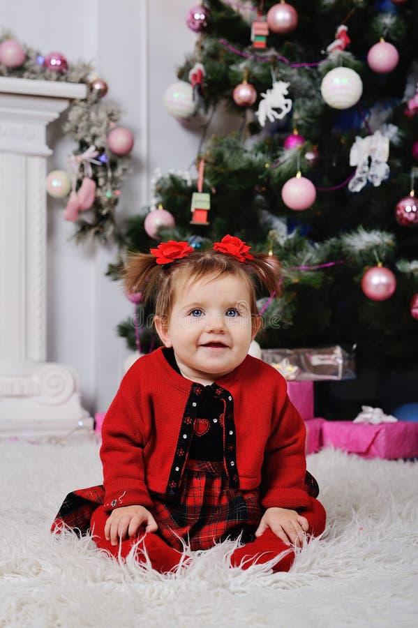 Niña en un vestido rojo en el fondo del árbol de navidad foto de archivo