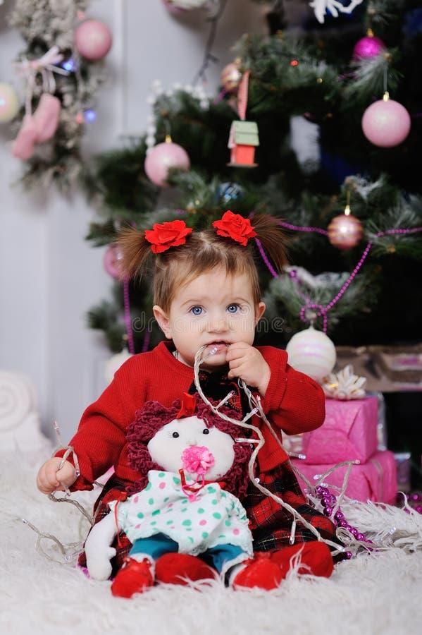 Niña en un vestido rojo en el fondo del árbol de navidad imagenes de archivo