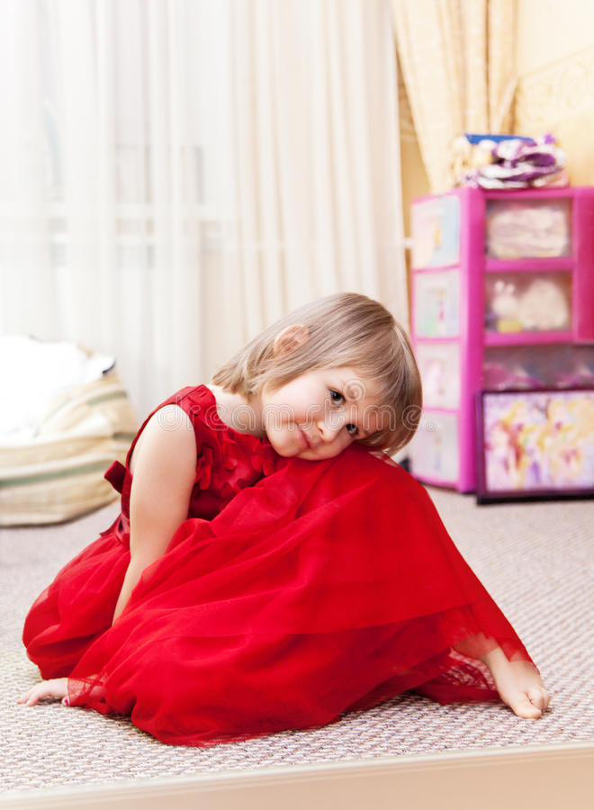 Niña en un vestido rojo hermoso que se sienta en su dormitorio fotos de archivo libres de regalías